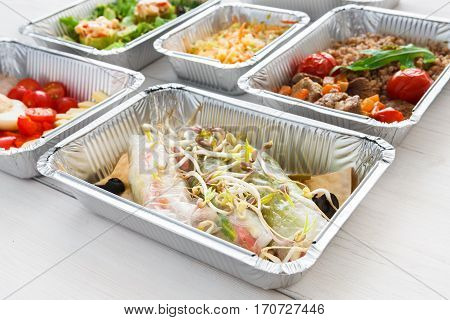Healthy food background. Take away of natural organic meals in foil containers. Fitness nutrition, fish, fresh vegetables and fruits. Restaurant dishes delivery