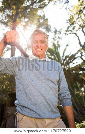 Portrait of happy mature male gardener carrying shovel on shoulder at garden