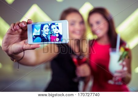 Smiling friends taking selfie with smartphone in nightclub