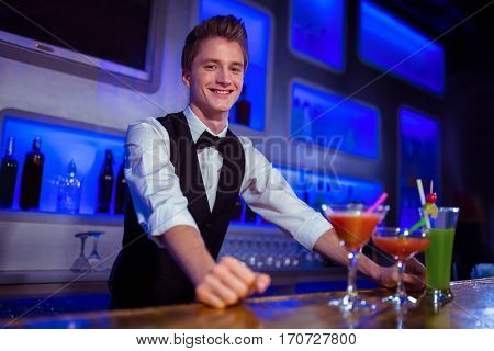 Portrait of smiling male bartender standing at nightclub