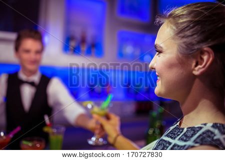 Barman serving cocktail to woman at nightclub