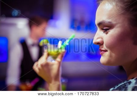 Young woman holding cocktail glass against bartender at nightclub
