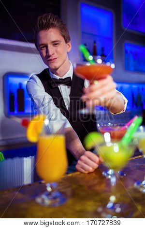 Portrait of smiling male bartender holding cocktail glass at nightclub