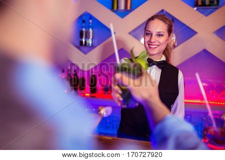 Young barmaid serving drink to male costumer at counter