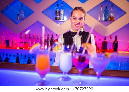 Portrait of pretty barmaid standing at illuminated bar counter