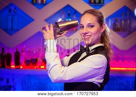 Portrait of beautiful barmaid with cocktail shaker at illuminated counter