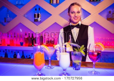 Portrait of breautiful smiling barmaid standing at nightclub