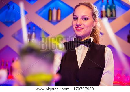 Portrait of beautiful barmaid holding cocktail glass at nightclub