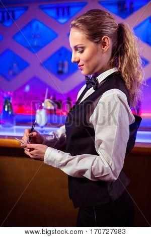 Beautiful bartender taking order at nightclub