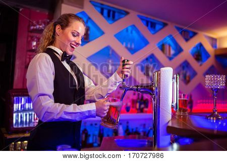 Happy barmaid pouring beer in glass at counter at bar