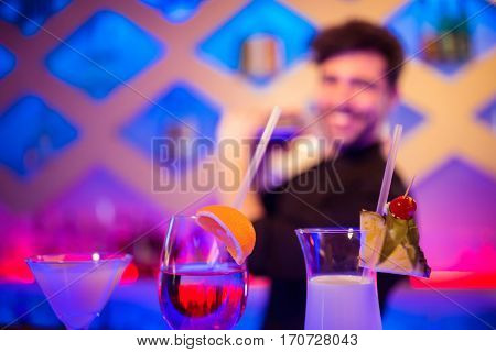 Various drinks on counter while barkeeper in background at bar