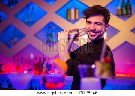 Portrait of handsome barkeeper preparing cocktail at bar counter