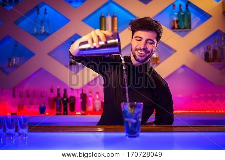 Confident barkeeper pouring cocktail in glass at bar counter
