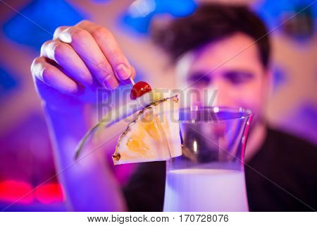 Bartender keeping fruits on cocktail glass at bar counter