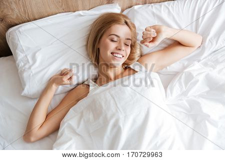 Top view of smiling woman waking up after sleep and stretching on bed with closed eyes