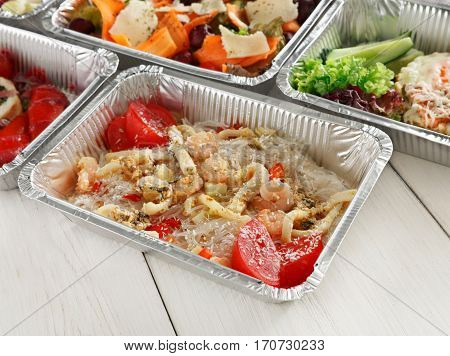 Healthy food background. Take away of natural organic food in foil boxes. Fitness nutrition, meat, rice vermicelli, vegetable salads and eggs.