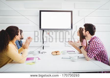 Happy young colleagues applauding while watching television during meeting at creative office