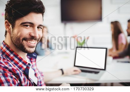 Portrait of confident young male executive with laptop in meeting room at creative office