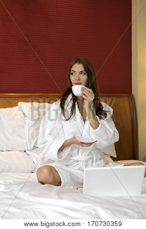 Beautiful young adult attractive and sensuality pretty brunette woman with cup on bed at bedroom