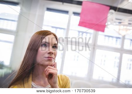 Thoughtful businesswoman looking on pink sticky note on glass in creative office