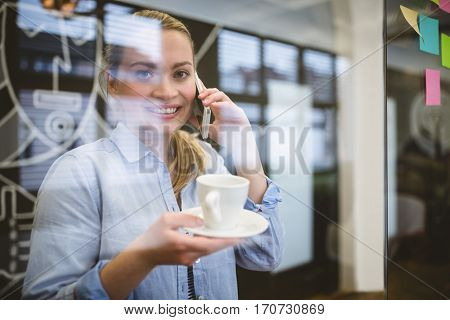 Portrait of businesswoman talking on phone during coffee break in creative office seen through glass