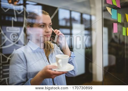 Businesswoman talking on phone during coffee break in creative office seen through glass