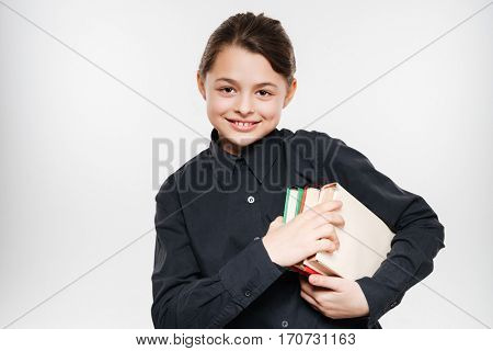 Image of pretty young girl holding books isolated over white background.