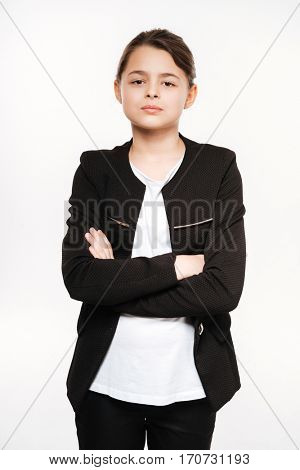 Image of serious young girl standing with arms crossed and posing isolated over white background.