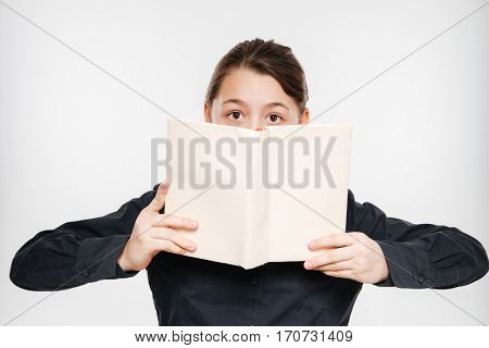 Photo of happy young girl reading book isolated over white background.