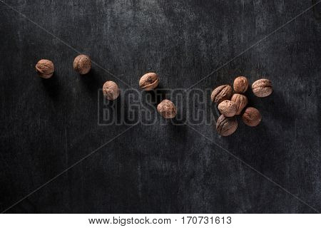 Top view photo of a lot of walnuts over dark background