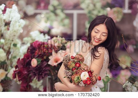 Beautiful girl in tender lacy dress with bouquet flowers peonies in hands standing against floral background in flower shop. Joyful asian female florist. Shy fashion model looking down and smiling.