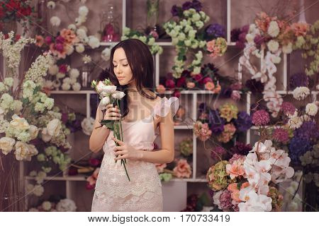Beautiful girl in tender pink dress with bouquet flowers peonies in hands standing against floral bokeh background in flower shop. Joyful asian female florist. Playful fashion model smells spring flowers.