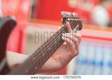 Women handle electric guitar playing chord focus