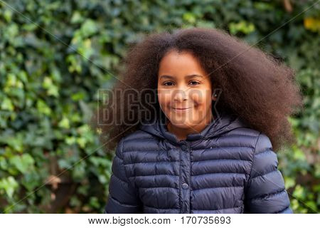 Pretty girl with long afro hair in the garden with a blue coat