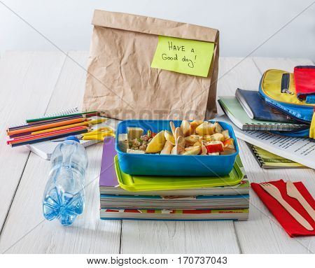 Healthy school lunch for child or teenager. Craft paper package, pile of exercise books, water, bag and food in lunch box on white wood table, cracker with cheese, nuts, oatmeal porridge and apples