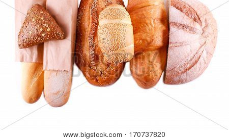 Different sorts of bread over white background top view