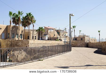 Akko (Acre) Israel. Street in the Old City of Acre - Israel. Palm trees modern street lights and ancient buildings.