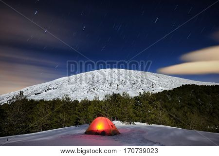 illuminated tent under the winter Etna mount and stars trails, Sicily
