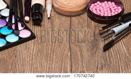 Makeup products on wooden surface with copy space. Colored eyeshadow, concealers, foundation, powder, blush, liquid eyeliner and mascara