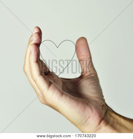 closeup of the hand of a young caucasian man holding the profile of a heart, against an off-white background
