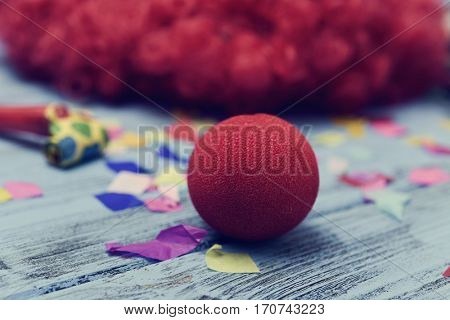 a curly red hair wig and a red clown nose forming the face of a clown on a rustic wooden surface full of confetti