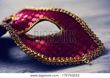 closeup of an elegant red and golden carnival mask on a rustic wooden surface