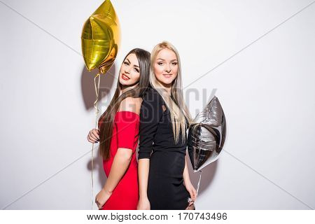Two smiling cute young women with balloons celebrating on white
