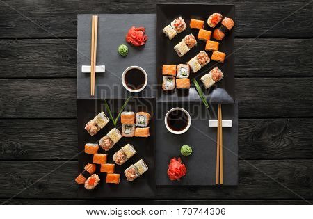 Japanese food restaurant, sushi maki gunkan roll platter. Set for two with chopsticks, ginger, soy, wasabi. Top view on rustic wood background and black slate plates.