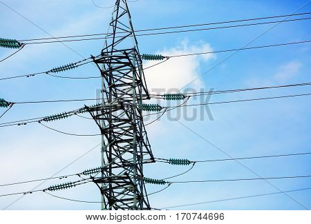 High voltage post. Electricity transmission pylon silhouetted against blue sky.