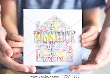 Child and adult person holding drawing consisting of words, closeup. Adoption concept