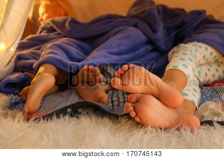 Feet of cute little children lying in hovel at home