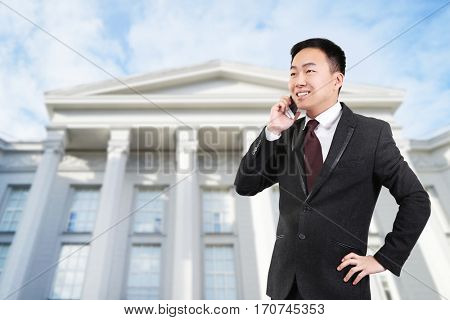 Law and justice concept. Young man talking on phone against courthouse background