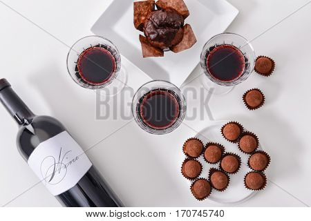 Delicious chocolate cake, truffles and red wine on white background