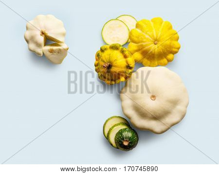Yellow, white and green zucchini, courgette and round pattipan squashes on blue background. Sorts of cucurbit top view